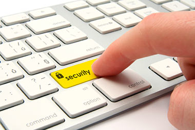 Computer key board with a yellow highlighted key with security written on it